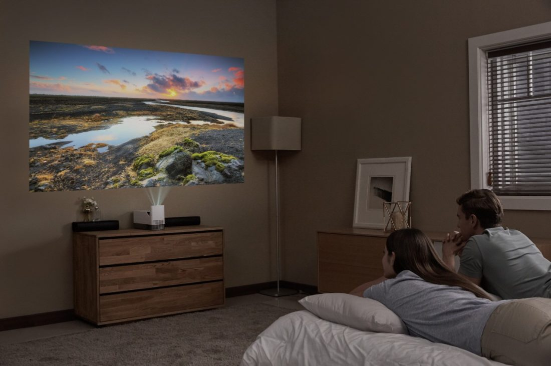 A couple lying in bed while watching a movie projected on the wall by the LG ProBeam Projector HF85J