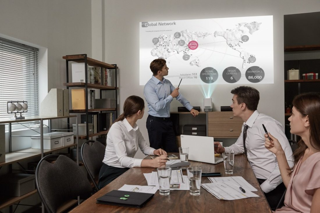 People in a business meeting watch a presentation that is being projected on the wall by the LG ProBeam Projector HF85J.