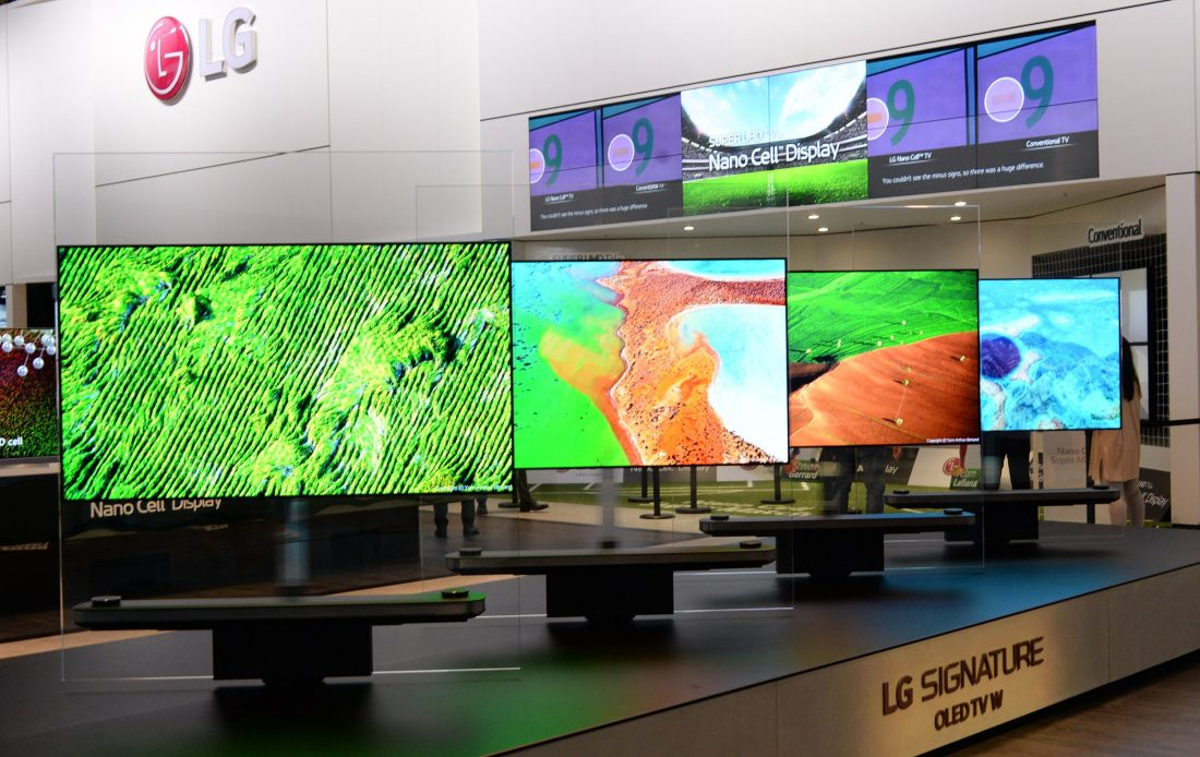 Four LG SIGNATURE OLED TV W sets are installed side by side on a display stand.