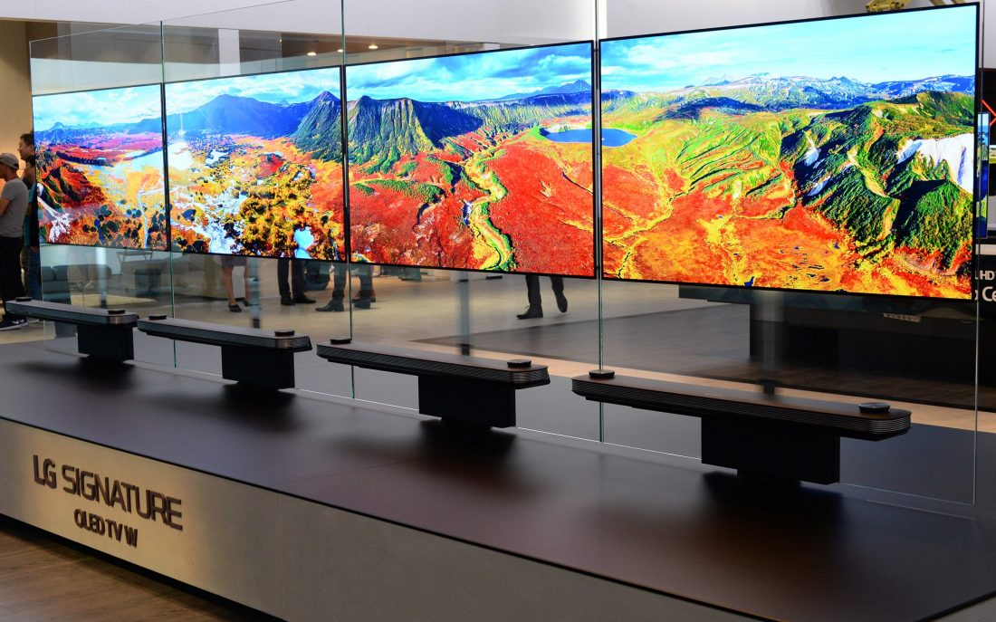 Another view of four LG SIGNATURE OLED TV W sets installed side by side on a display stand.
