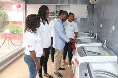 A man explains LG washing machine features to the event's attendants during public event.