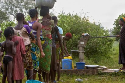 People wait in line to fetch the water from the public well.