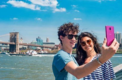 A man and woman taking a selfie in front of a riverfront with the LG G7 ThinQ in Raspberry Rose