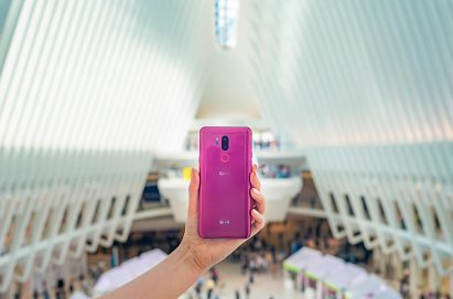 A person holding the LG G7 ThinQ in Raspberry Rose with the rear view showing