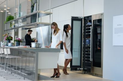 Man opening refrigerator, woman opening wine cellar and another woman trying the induction cooktop at SIGNATURE KITCHEN SUITE's exhibition hall cooperated with Arclinea at IFA 2018
