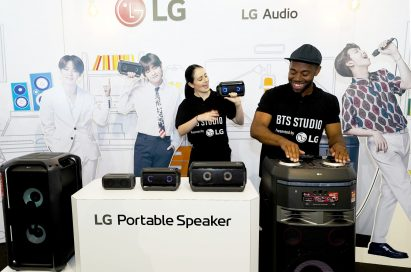 A man and woman both test LG's speaker products at the BTS Studio Presented by LG.