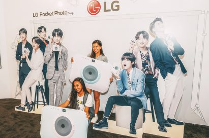 Visitors take a picture at the LG Pocket Photo Snap booth with cutouts of their favorite K-pop group.