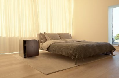 LG OBJET Refrigerator positioned next to a bed in an apartment