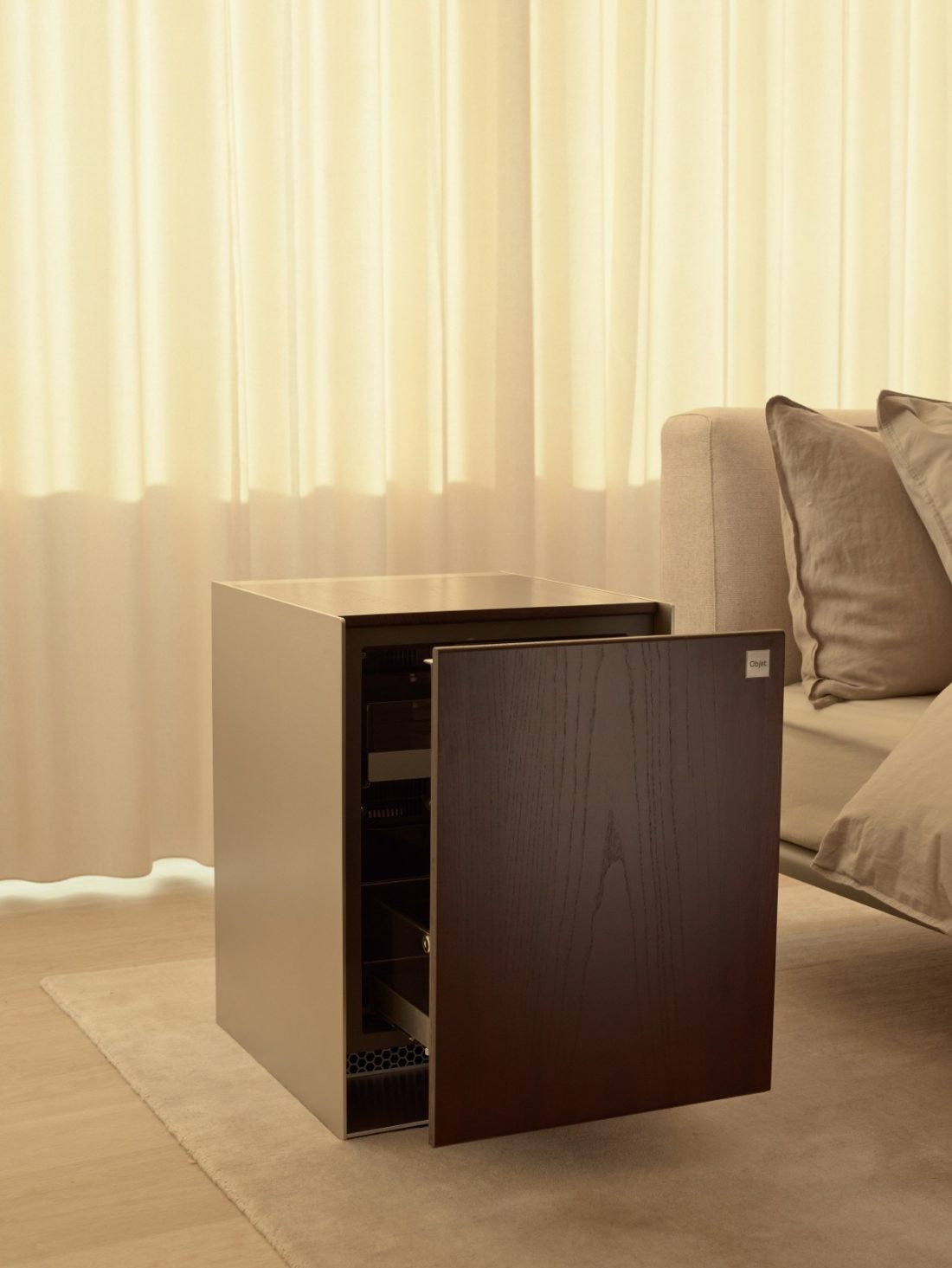 Close-up view of the LG OBJET Refrigerator with the bed visible to its right