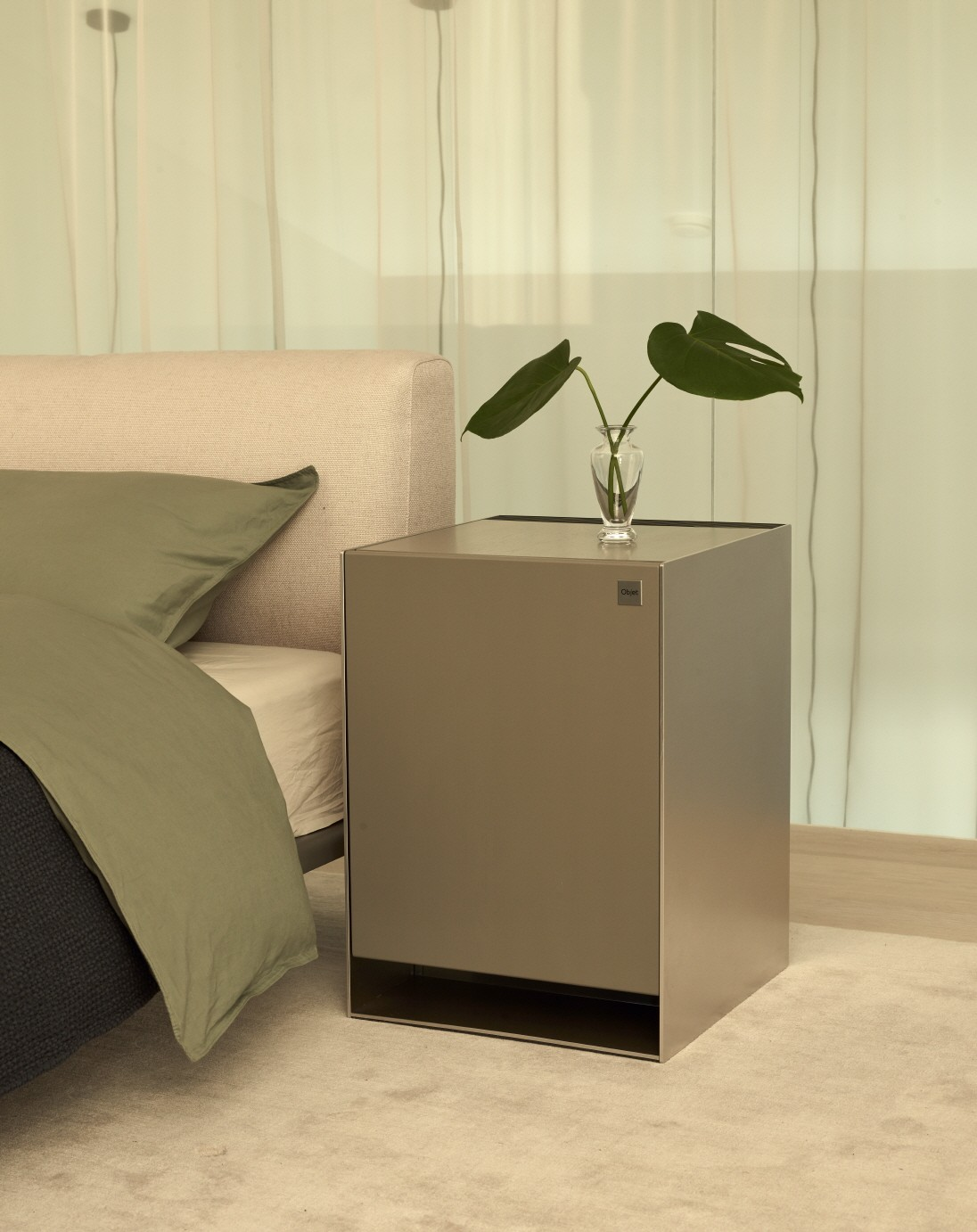 LG OBJET Air Purifier with a plant placed on top of it positioned next to a bed