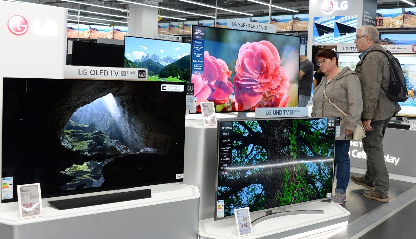A consumer examines the highly thin depth of LG's SUPER UHD TV while some other consumers look around other TV products at LG's store.