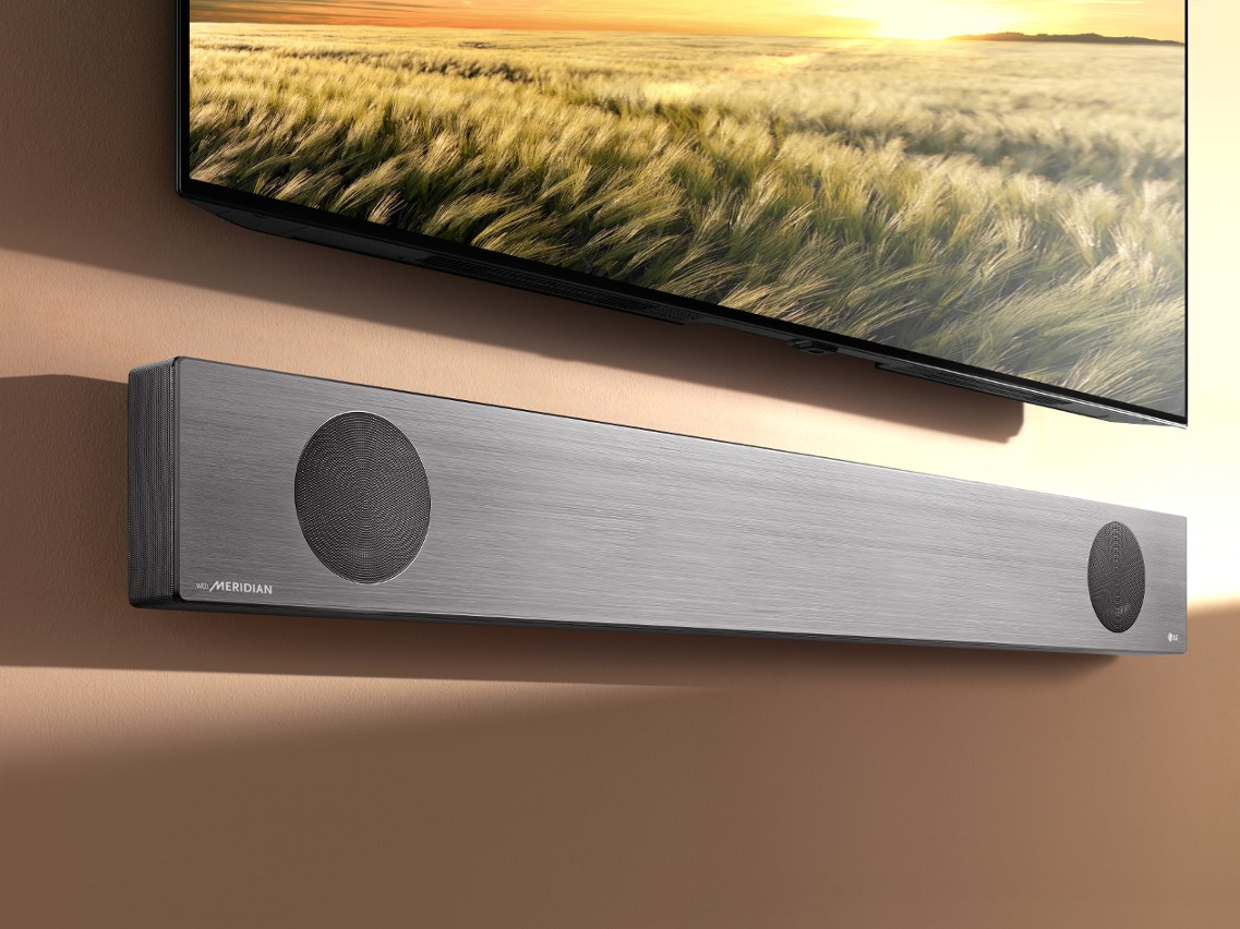 LG Soundbar model SL9YG fixed to a wall below an LG TV
