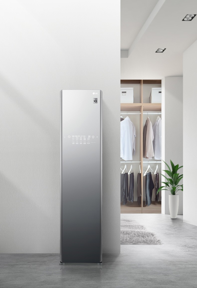 LG Styler Black Tinted Mirror Glass Door in a home with clothes hanging on a closet in the background