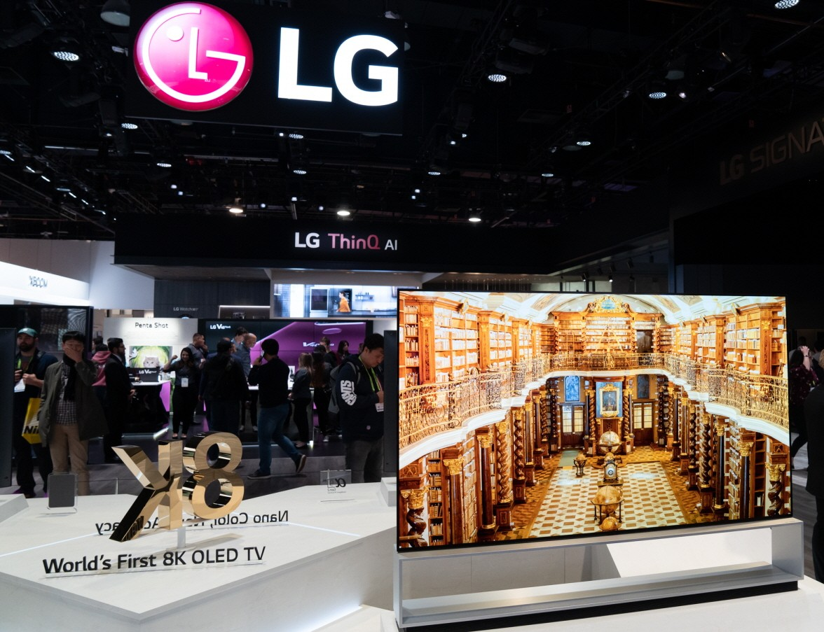 """Front view of an LG 8K OLED TV set positioned on the right side of a promotional sign saying """"World's First 8K OLED TV"""""""