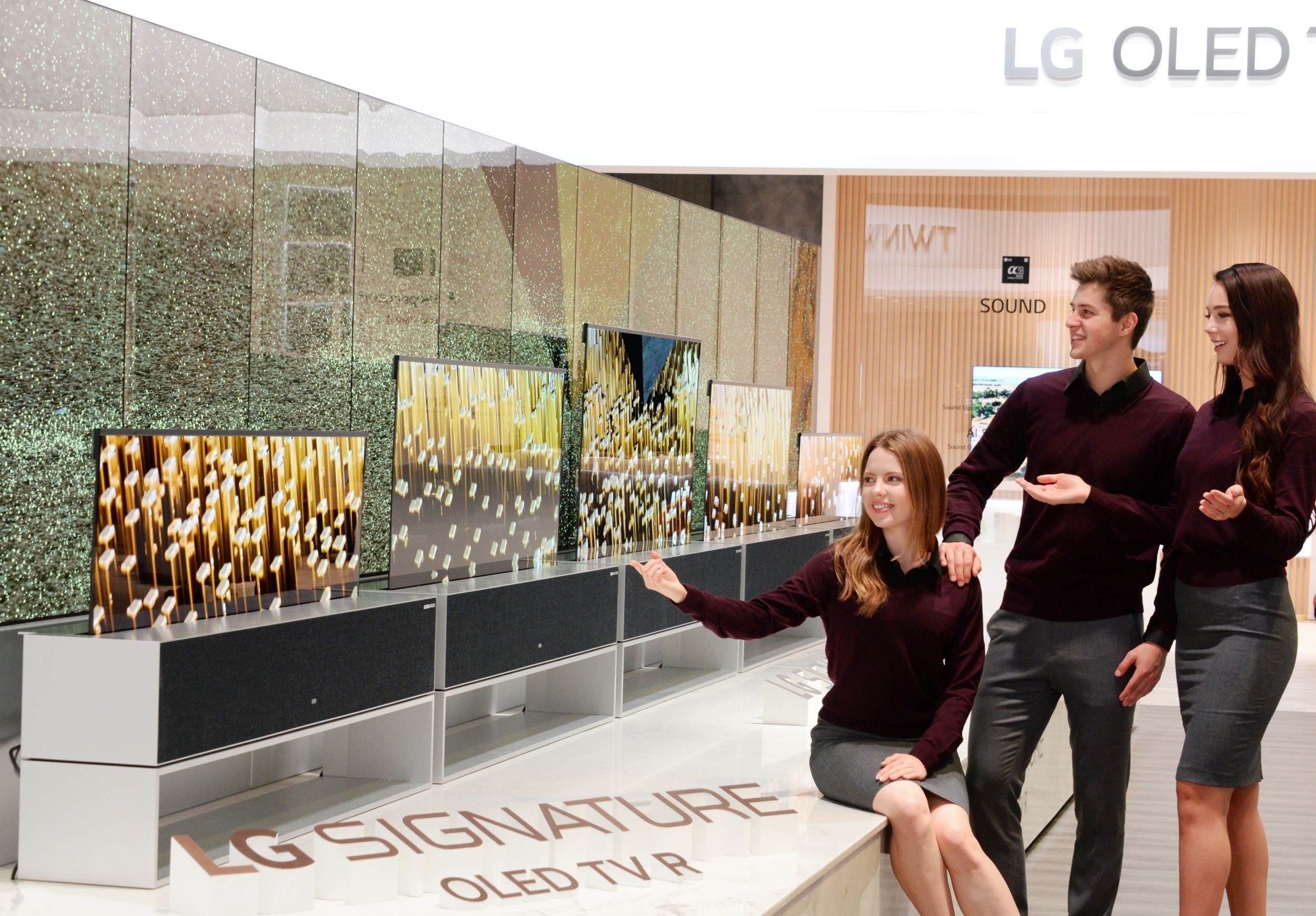 Three people are looking at LG OLED TV R on display at LG's CES 2019 booth