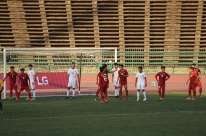 Players wait for a corner-kick inside the penalty box and there is LG's pitch-side advertisement board behind the goal.