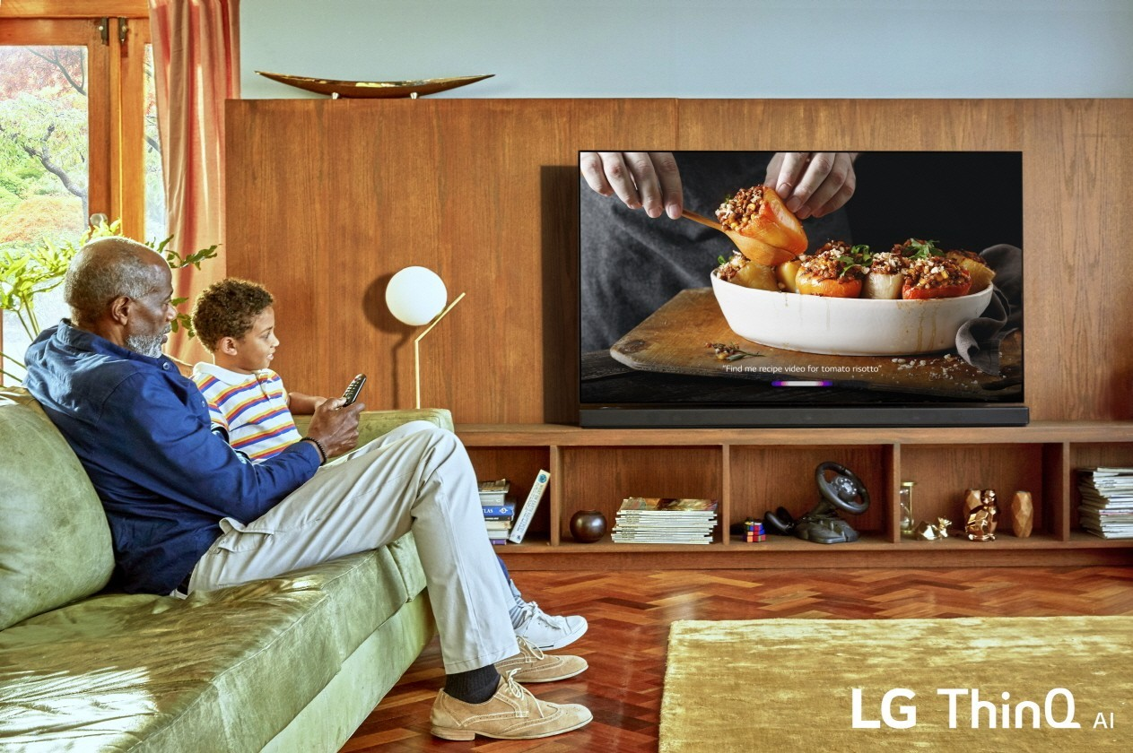 A grandfather watches the LG ThinQ AI TV at home with his grandson