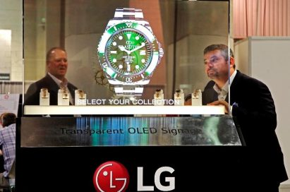 Two NAB Show attendees behold the LG Transparent OLED display which shows a piece of watch.