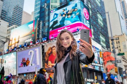 A woman holds the LG G8 ThinQ out to take a selfie in Times Square, New York.