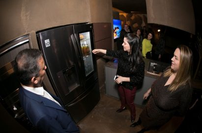 Visitors discuss the LG SIGNATURE InstaView Door-in-Door Refrigerator at LG's Planet Home.