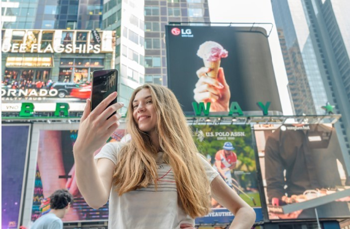 A woman takes her selfie with the LG V50 ThinQ in Times Square, New York.