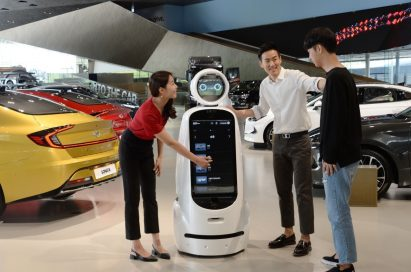 Three visitors interact with LG CLOi GuideBot in front of vehicles at Hyundai Motor Studio Goyang.