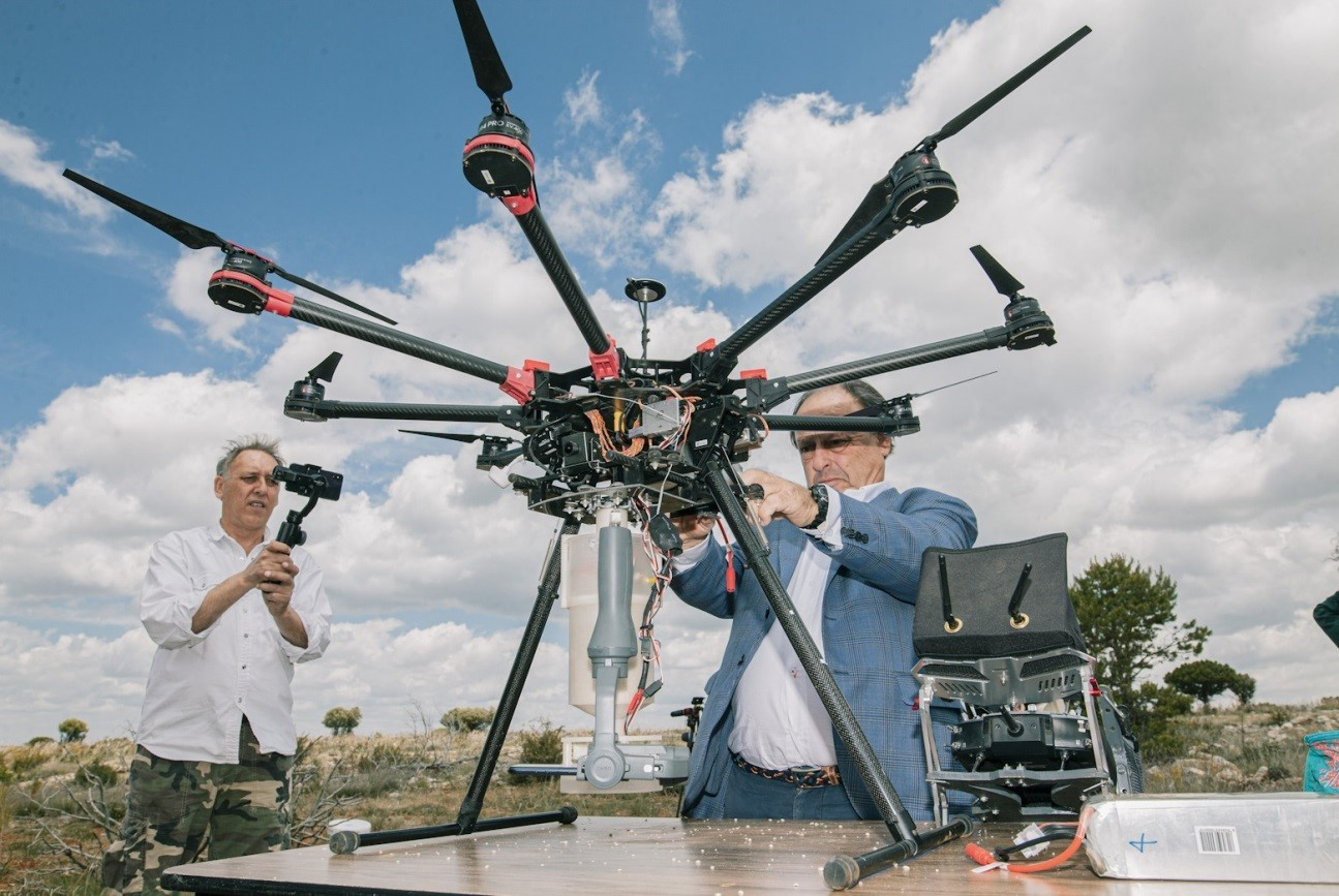 A project's associates equip the drone with some analytic devices while another man records it with a camera.