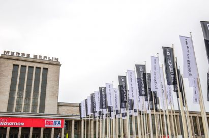 "Partial view of Messegelände Berlin ExpoCenter City with promotional flags of the LG SIGNATURE brand and its brand theme ""The Art of Essence"" flying in front"