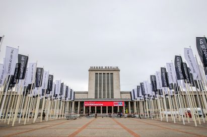 """Front view of Messegelände Berlin ExpoCenter City with promotional flags of the LG SIGNATURE brand and its brand theme """"The Art of Essence"""" flying in front"""