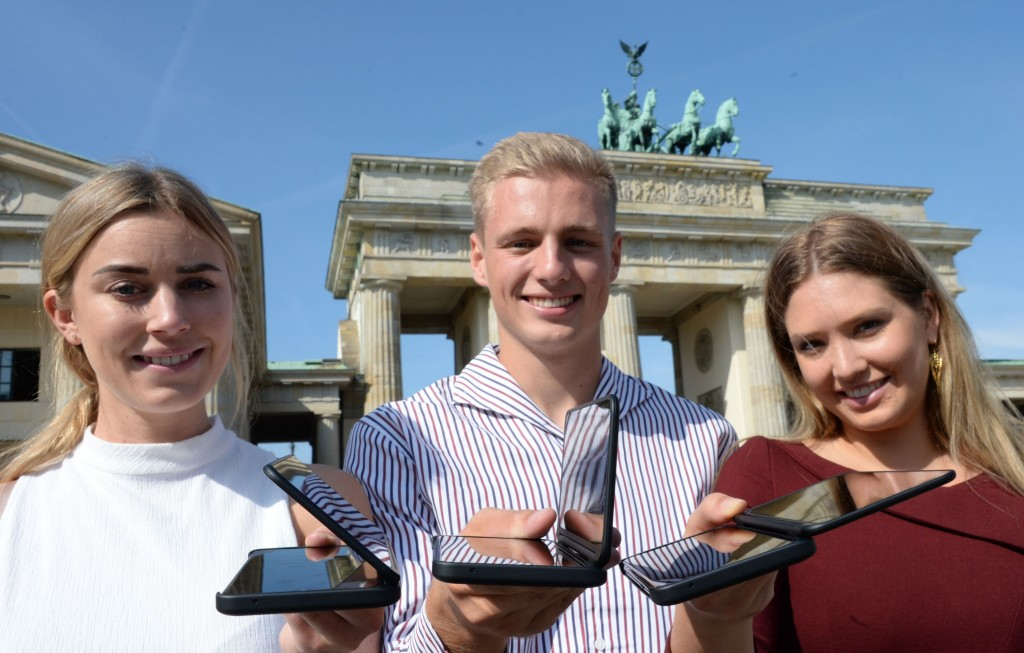 Two women and one man stand in front of the Brandenburg Gate each holding LG G8X ThinQ smartphones.