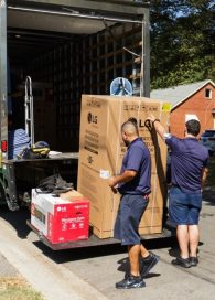 Two volunteers unload LG-donated home appliances from the container of a truck.