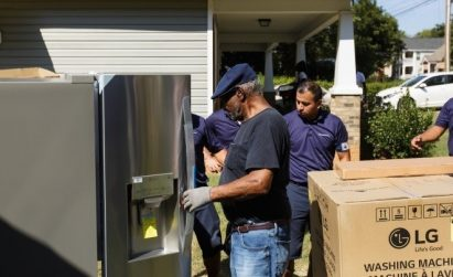 A group of volunteers check and assemble parts of LG-donated home appliances.