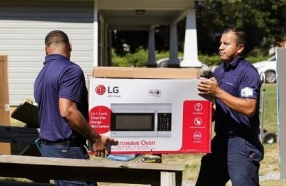 Two volunteers carry LG's microwave oven to bring it into a house of Charlotte's Druid Hills neighborhood.