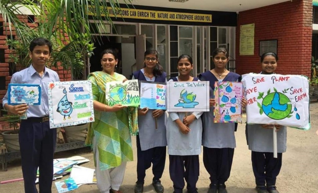 Standing next to a teacher, five students hold up their paintings with some catch phrases to encourage water conservation.