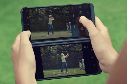 A man holds LG G8XThinQ with LG Dual Screen in her two hands horizontally to watch the golf swing video on the golf course.