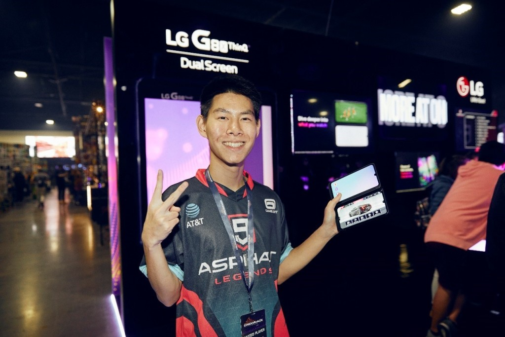 A contender poses while holding the LG G8X ThinQ with Dual Screen in front of the smartphone and dual screen's display zone.