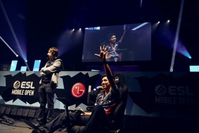 A gamer waves to spectators as he sits on a gaming chair center stage.