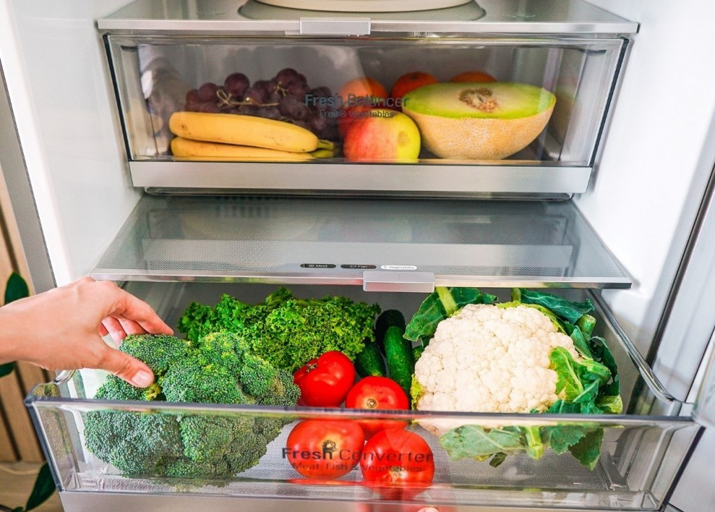 A close-up of LG V+ refrigerator's innovative Fresh Balancer drawer on top of an opened Fresh Converter drawer, the former holding fruits and the latter storing vegetables.