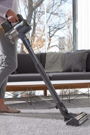 A closer look at LG CordZeroThinQ A9 Stick Vacuum as a woman uses it to clean her living room carpet.