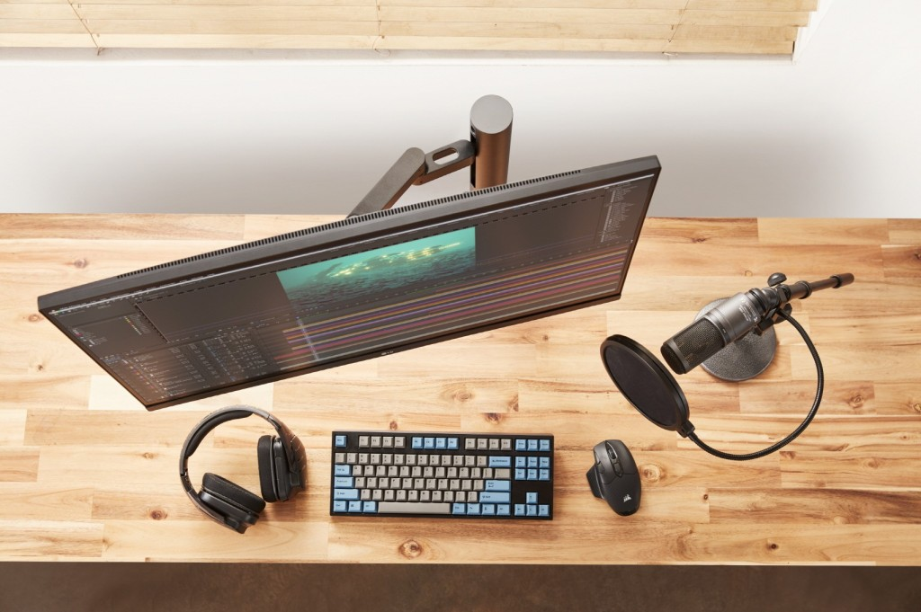 High view of LG UltraFine Monitor 32UN880 completing a desk setup comprising a keyboard, mouse, professional microphone and headphones