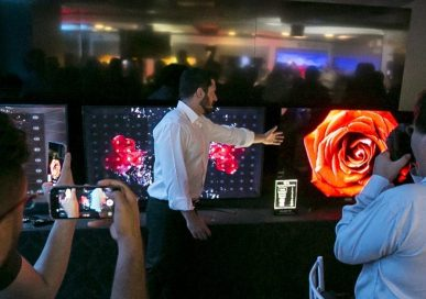LG's Pedro Valery compares the picture quality of the LG OLED TV with that of products from other brands at Lab Tech LG, as reporters record videos and take pictures.