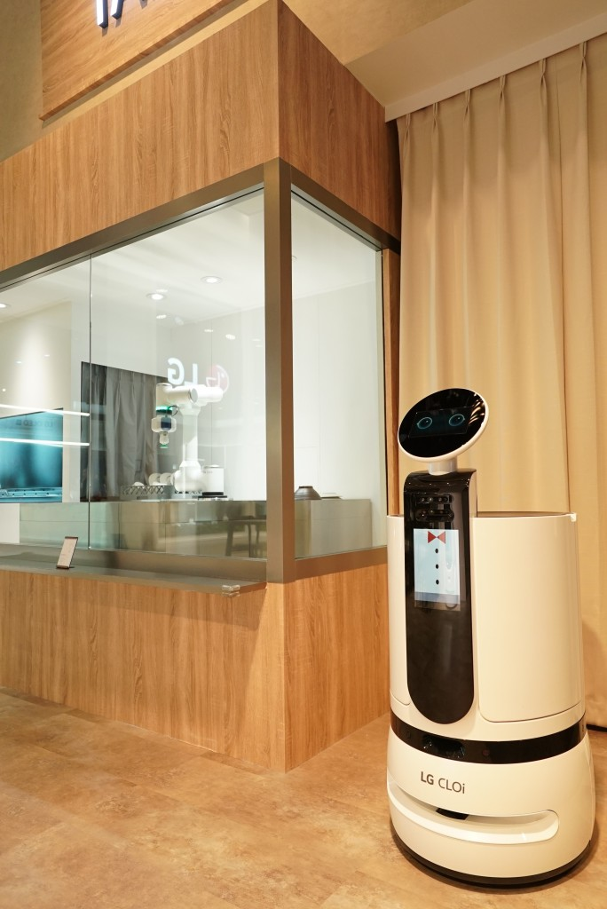 A closer look at the LG 'CLOi's Table' restaurant with a server bot, and the LG CLOi CoBot ready to clean the dishes in the background, at CES 2020