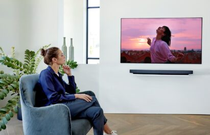 A woman watches a movie on LG's Wallpaper series OLED TV model WX that boasts immersive picture quality