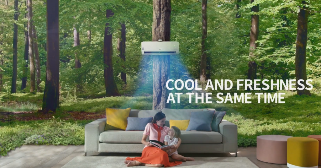 A picture of woman and child reading a book as they sit under LG DUAL COOL, as if they're sitting in the middle of a dense forest