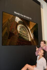 Another view of the World's First 8K OLED TV display at IFA 2018, with a male and female model sitting below and pointing up to the screen