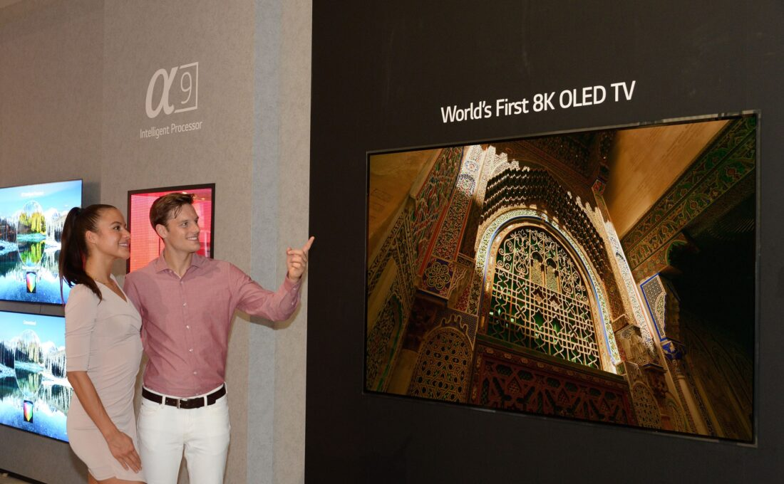 Another view of the World's First 8K OLED TV with A9 Intelligent Processor display at IFA 2018, with a male and female model standing on the side pointing to the screen