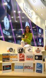 An LG promotor at MWC 2016 holds the LG G5 in her hand while standing behind 15 Best of MWC awards for the LG G5