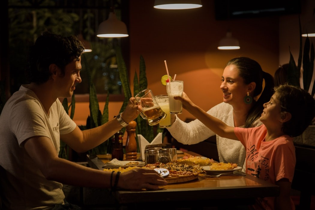 A family 'cheers' as they eat around the dinner table under dim lighting