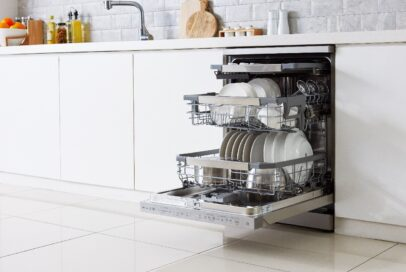 A view of a fitted LG Dishwasher with QuadWashTM the door open to show it full of clean dishes, pots and glasses
