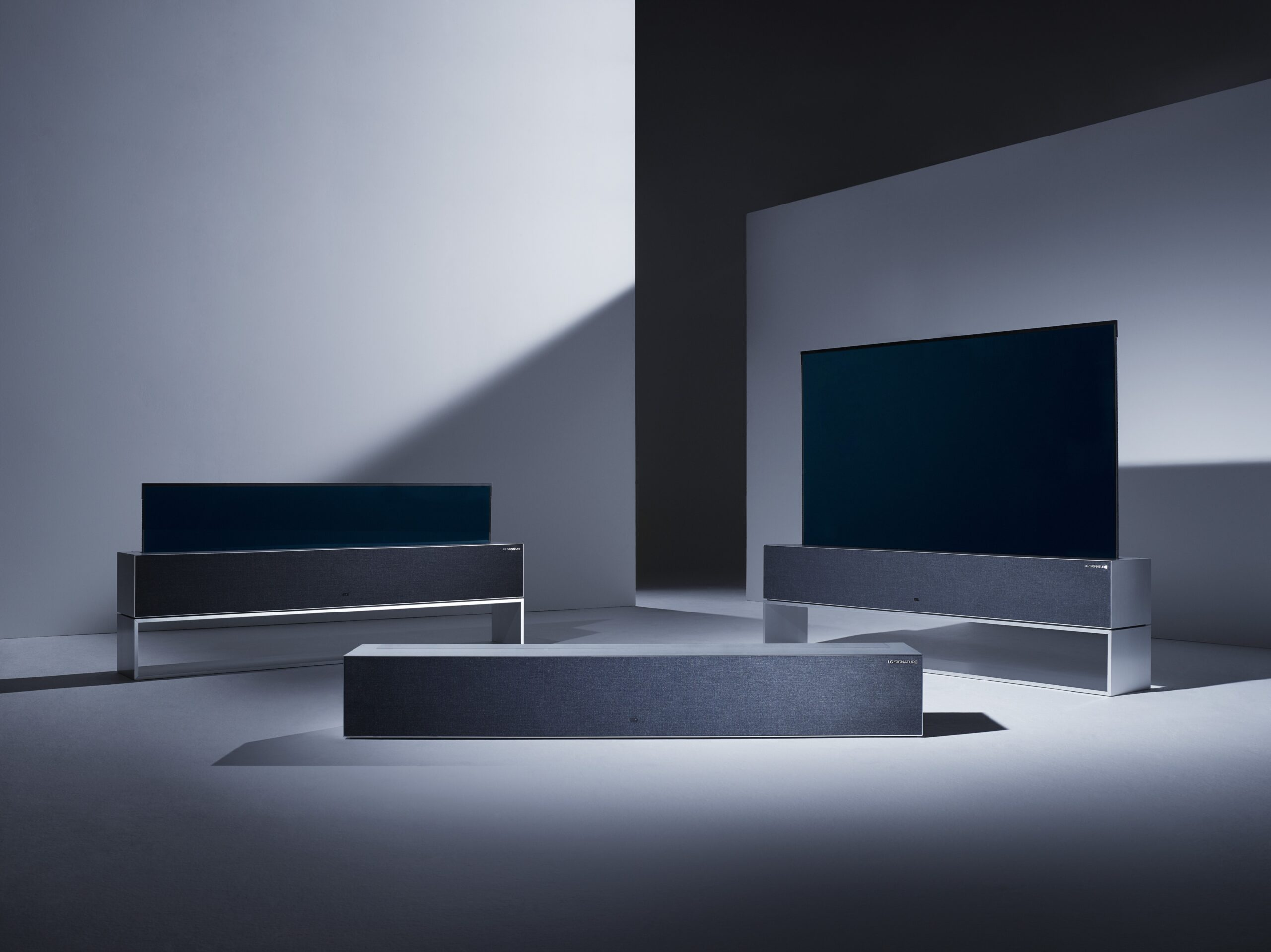 Three LG SIGNATURE OLED TV R sets are set in three different stages of unfurling their rollable displays at a darkened studio.
